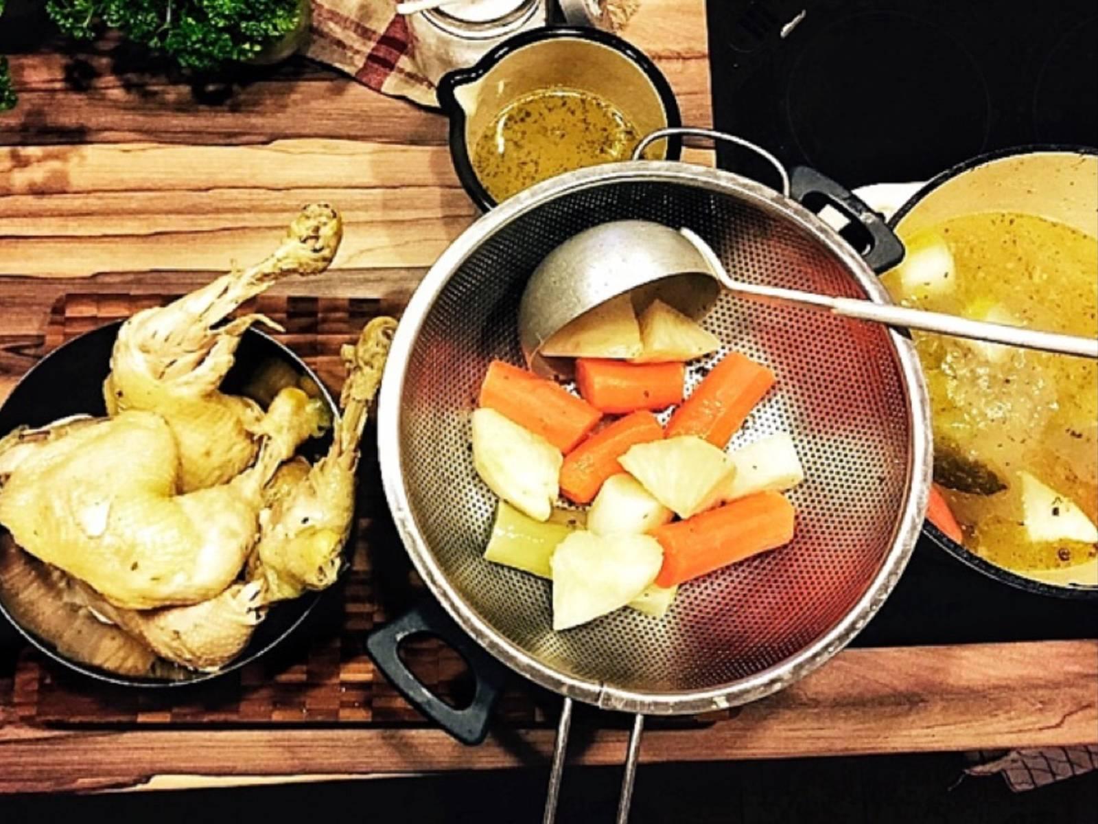 Fleisch aus der Brühe entnehmen und Brühe durch ein Sieb gießen, sodass nur die klare Hühnerbrühe übrig bleibt.