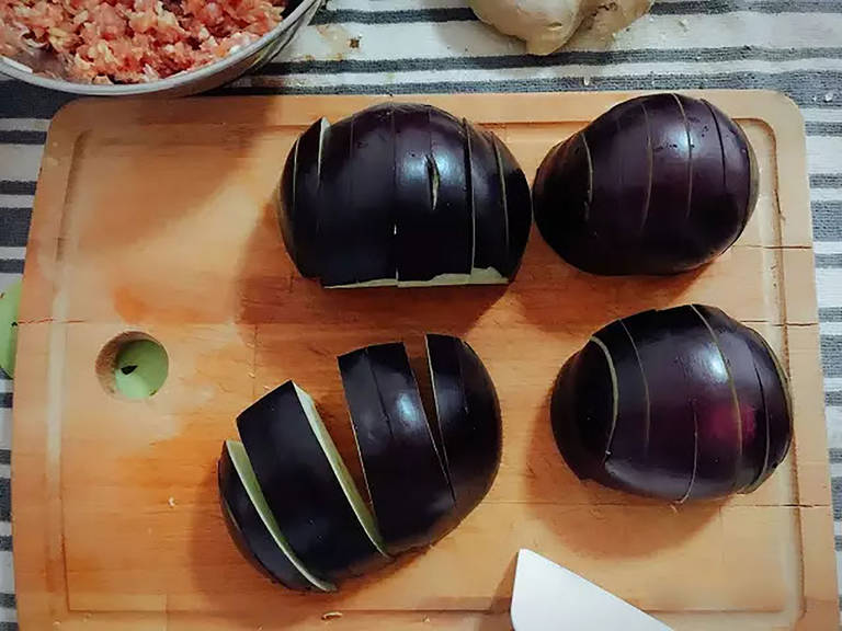 Halve the eggplant lengthwise. Cut each half into thick slices. Then make a deep slit in each slice to make a pocket within the eggplant's flesh.