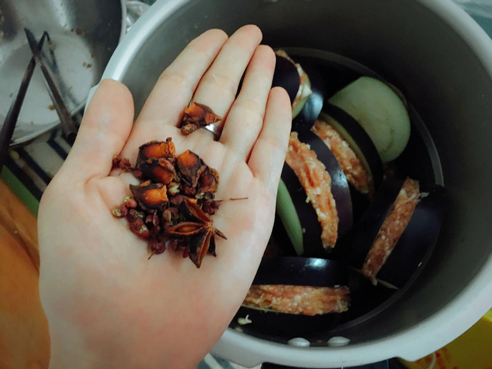 将填上馅的茄盒放入蒸笼,一个个摆好排排站。调馅的碗加适量水制作底汤倒入锅,防止糊底。锅中加入八角和四川花椒粒。