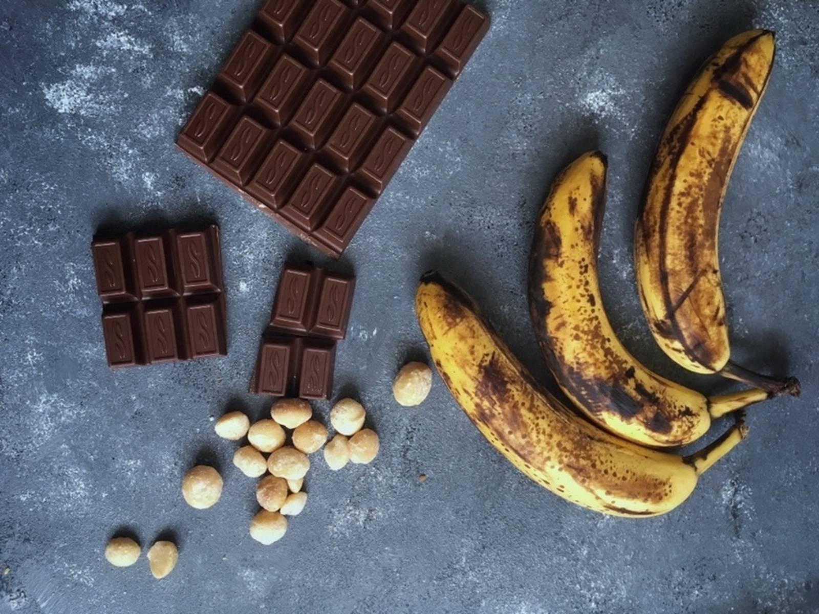 Backofen auf 175°C vorheizen. Zunächst in einer Schüssel die meisten Bananen mit der Gabel zermatschen. Dann mit dem Schneebesen Vanille, Zucker und Salz unterrühren. Das Kokosöl und die Hälfte der Schokolade schmelzen und unterrühren.
