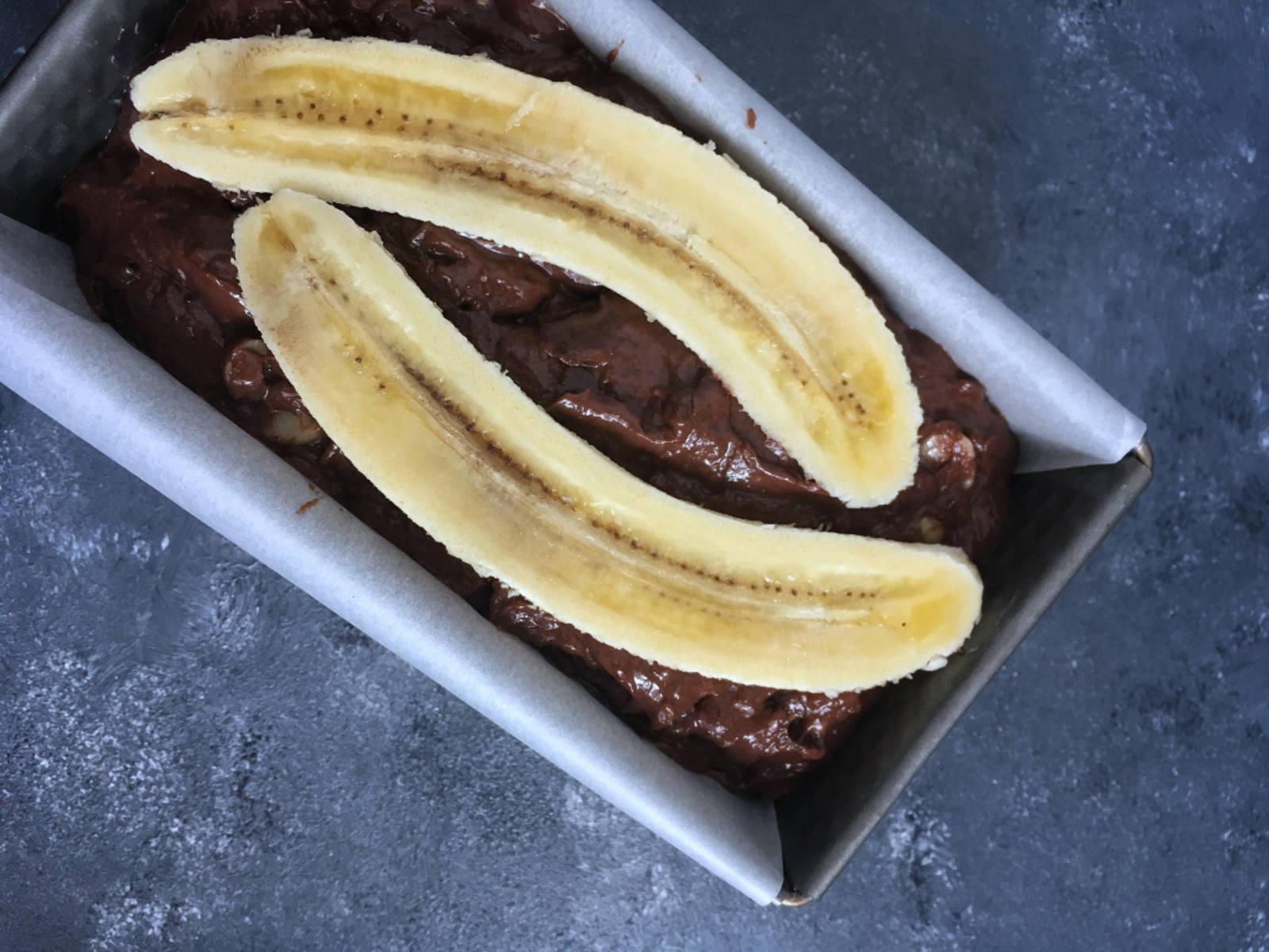 Den Schokoteig in die Form geben. Dann die übrige Banane der Länge nach halbieren und mit dem braunen Zucker bestreuen. So karamellisiert das beim Backen so schön.