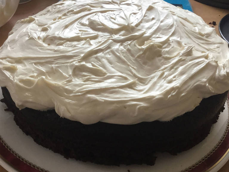 To make the frosting, lightly whip the cream cheese until it is smooth. Sift the powdered sugar into the cream cheese and beat them together. Add heavy cream and further beat to achieve a spreadable consistency. Spread the frosting on the cooled cake and serve.