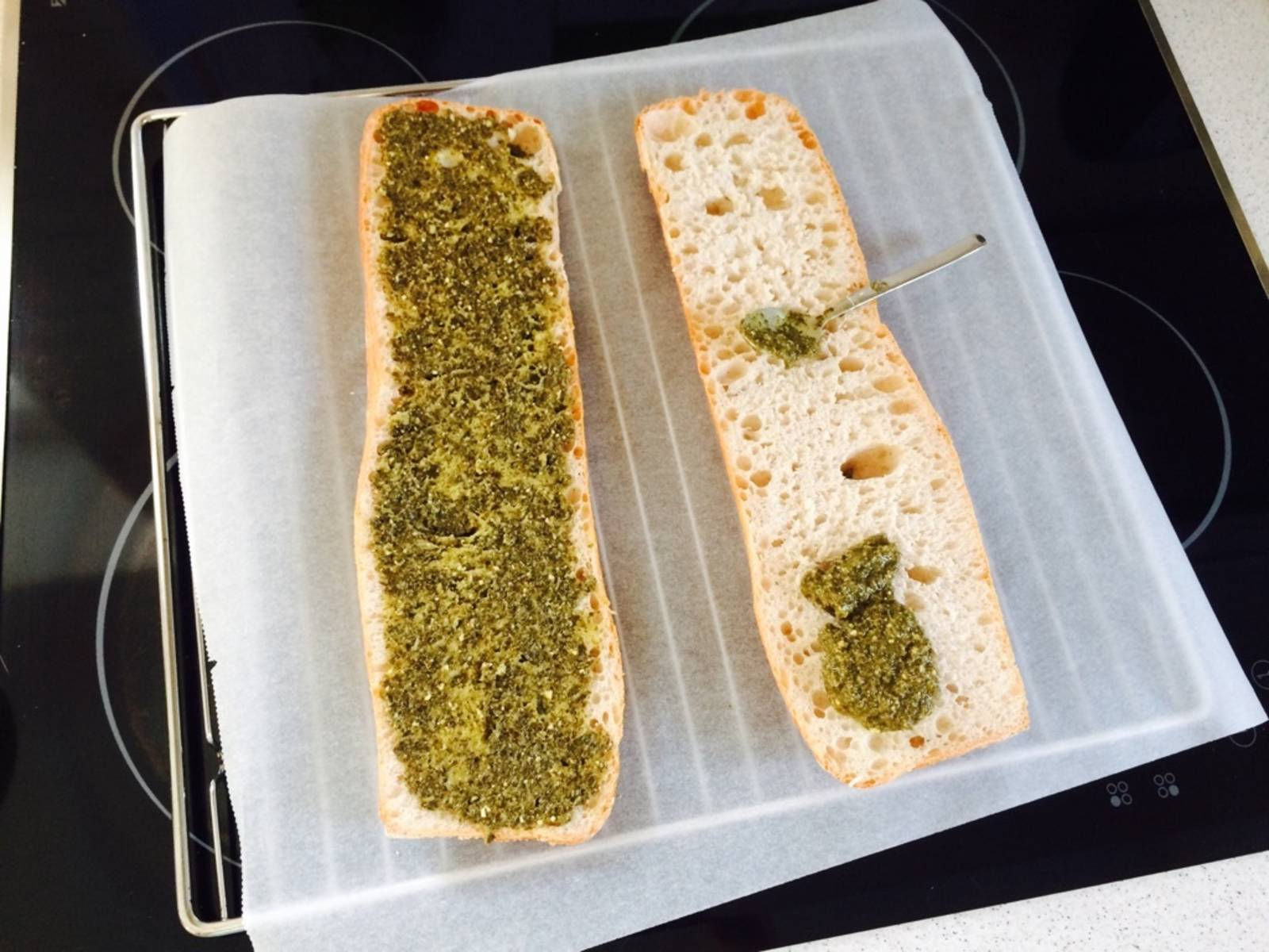Pre-heat the oven to 200°C/390°F. Halve ciabatta and spread pesto on top.