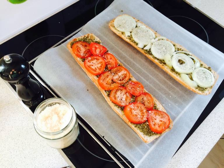 Slice tomatoes and onion, lay over the ciabatta, then season with salt and pepper.
