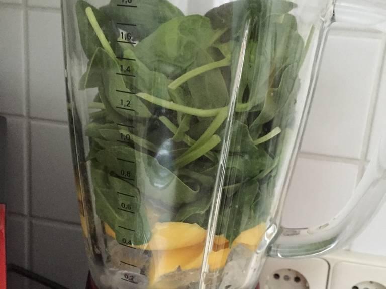 芒果剁碎。往搅拌机里倒满冰块,放入芒果和嫩菠菜。