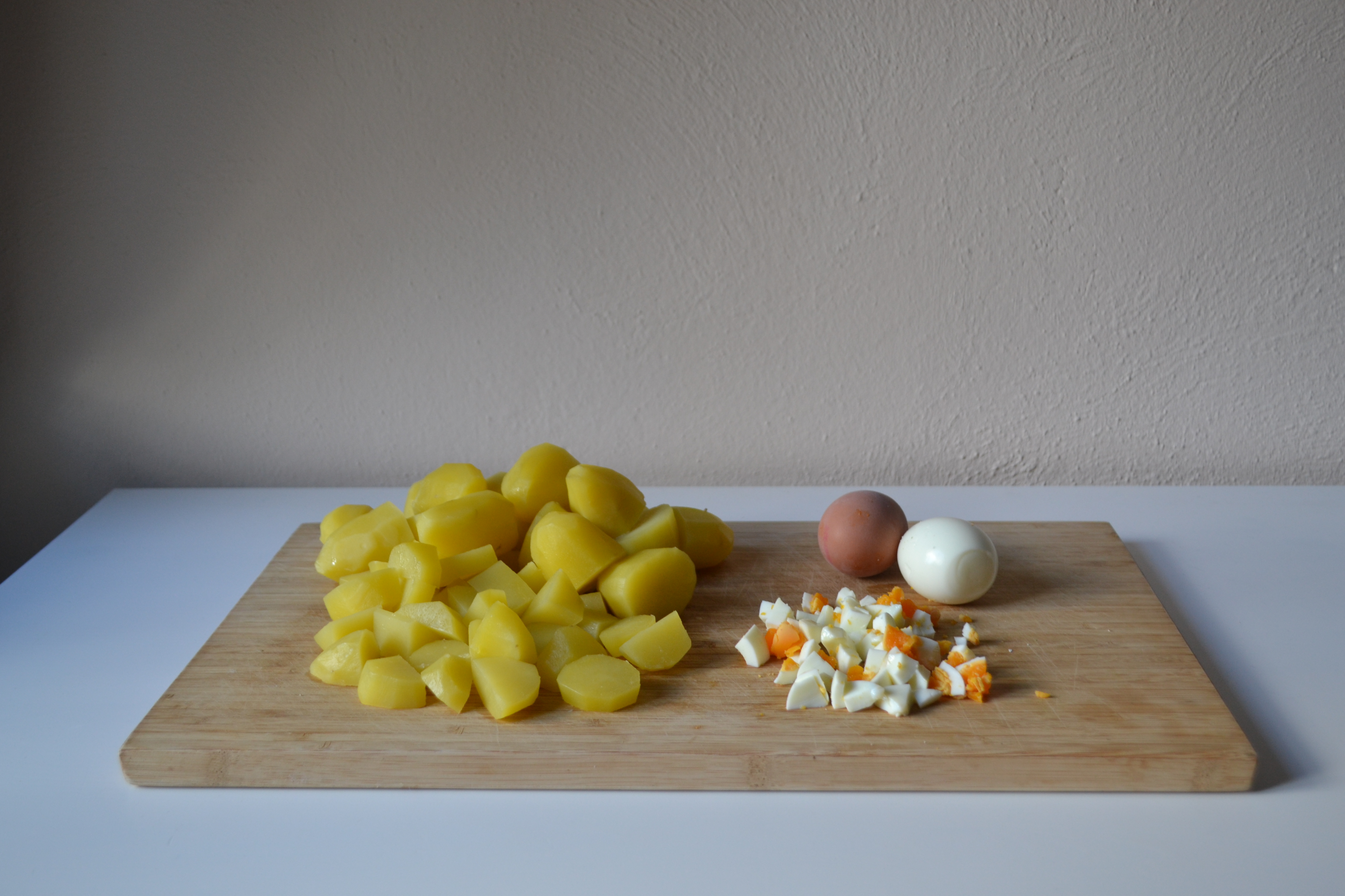 Peel and finely dice cold eggs. Cut potatoes in large chunks (to preference). Put them in a large bowl, together with the pickles and apple pieces.