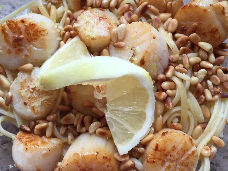 Mix the hot pasta with the with lemon-oil mixture. Serve with pine nuts, basil, and scallops. Enjoy!