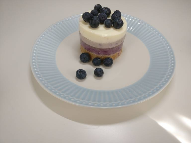 Repeat this process for the remaining light violet-colored mixture and the white mixture. Allow each layer to cool well, and transfer the cheesecakes to the fridge overnight. To serve, gently remove the dessert rings and decorate with fresh blueberries. Enjoy!