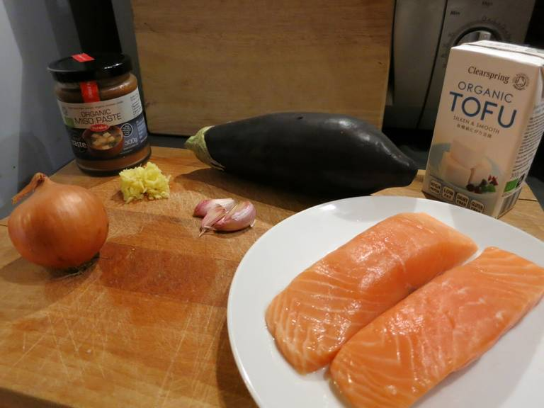 Dissolve miso paste in hot water in a large bowl. Peel and chop ginger and add to the bowl along with salmon fillets. Set aside to marinate.