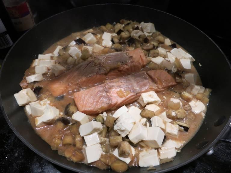 Zwiebel und Knoblauch fein hacken und Aubergine in Würfel schneiden. Olivenöl in eine Pfanne über mittlerer Hitze geben und Zwiebel, Knoblauch und Aubergine darin ca. 5 Min. anbraten. Lachfilets zusammen mit der Marinade in die Pfanne geben, die Hitze reduzieren und abgedeckt ca. 15 Min. köcheln lassen, oder bis der Lachs gar ist. Seidentofu würfeln, in die Pfanne geben und ca. 2 Min. weiterkochen. Anschließend servieren und genießen. Guten Appetit!