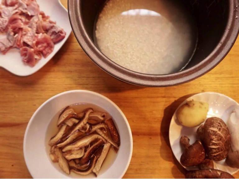 Shiitake Pilze in eine kleine Schüssel geben, kochendes Wasser darüber gießen und ziehen lassen. Ingwer in dünne Streifen schneiden. Frische Shiitake Pilze und Kräuterseitling klein schneiden. Knochen der Hähnchenschenkel entfernen und das Fleisch in Stücke schneiden.