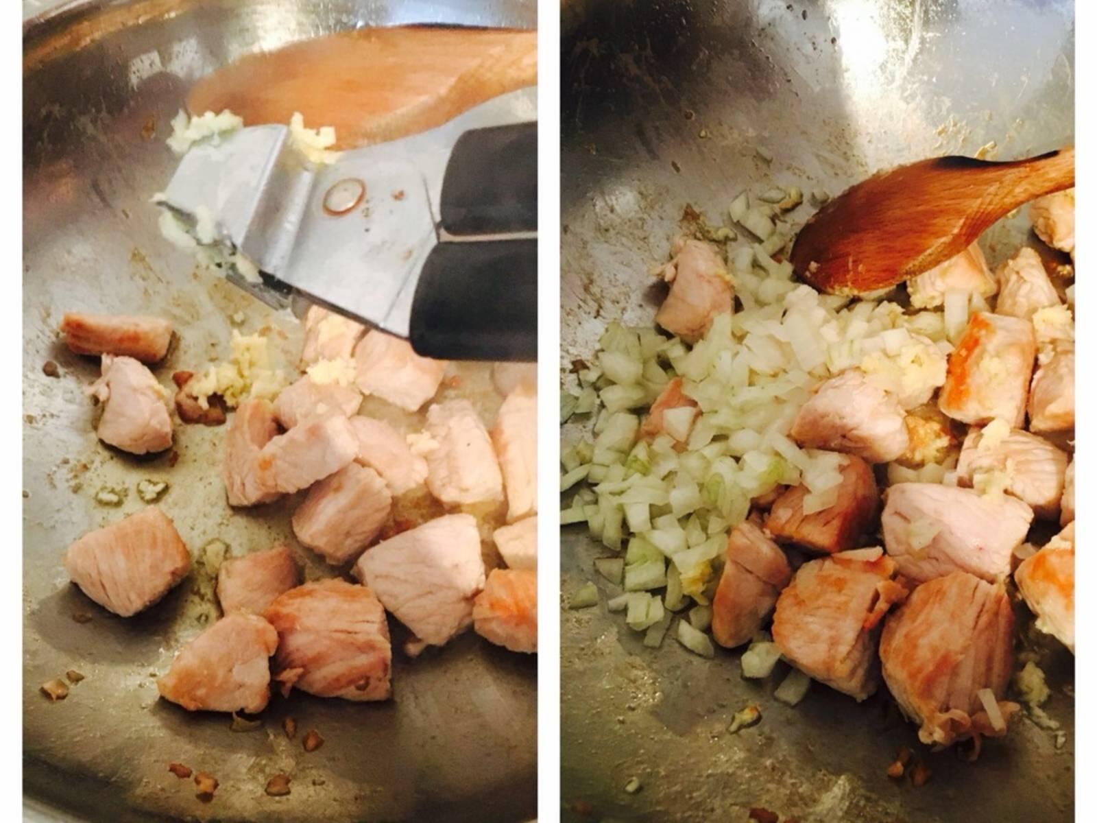 Das Fleisch in mundgerechte Stücke schneiden. In einer großen Pfanne das Ghee erhitzen und das Fleisch darin braun braten. Zwiebeln und Teil des Knoblauchs fein hacken und zum bratenden Fleisch geben.