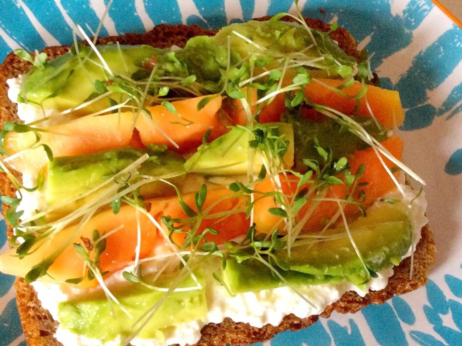 将农家芝士抹到两片面包上,往上摆木瓜片和牛油果片,佐以水芹,夹好三明治,然后尽情享用吧!