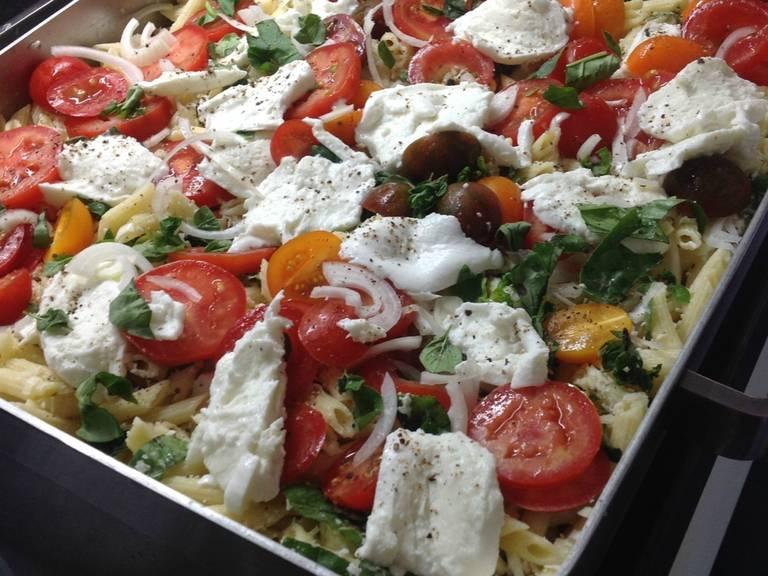 将三分之一的马苏里拉奶酪和剩余的帕马森干酪屑拌入烤盘里的食材中。撒盐与胡椒调味。最后,在顶上倒入剩余的马苏里拉奶酪、番茄、洋葱、剩余的罗勒和牛至叶片。再次撒盐与胡椒,淋上橄榄油。将烤盘放入烤箱低层,以200℃烤35-40分钟。尽情享用吧!