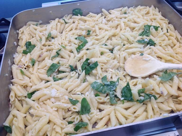 在一锅水中撒盐,倒入通心粉,煮至具有弹牙嚼劲。与此同时,将柠檬擦出皮碎,帕马森干酪擦屑。大略剁碎罗勒。剁碎凤尾鱼和蒜,将它们和柠檬皮碎、马斯卡帕尼乳酪、半份帕马森干酪屑和半份罗勒末搅拌混合。将意面和奶酪混合物一起倒入烤盘中,搅拌均匀。