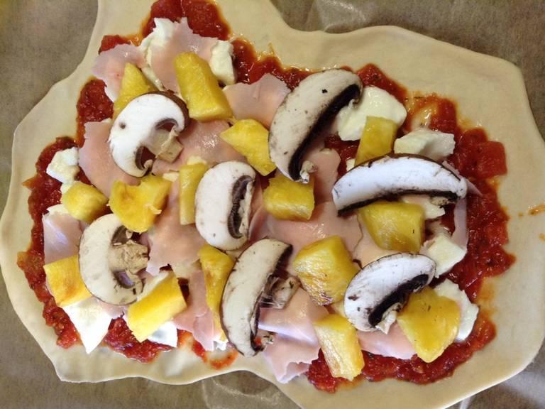 Für den Belag den Schinken in kleinere Stücke schneiden und Champignons und Ananas in Scheiben schneiden. Schinken, Champignons und Ananas auf der Pizza verteilen. Falls du Ananas aus der Dose verwendest, muss sie vorher gut abtropfen, damit sie den Pizzateig nicht aufweicht.