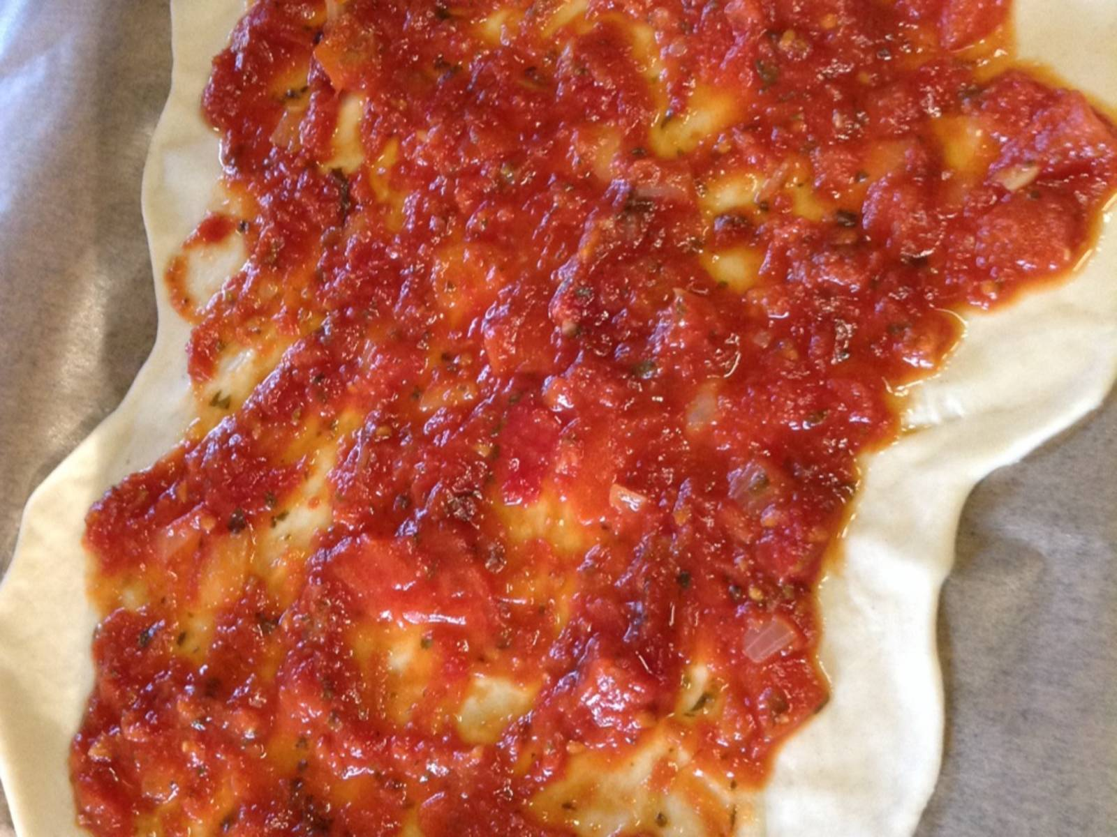 Cover dough with cold pizza sauce, leaving a 2-cm/0.8-in. thick crust. Make sure you don't apply too much sauce or leave gaps. Use more or less sauce if needed.