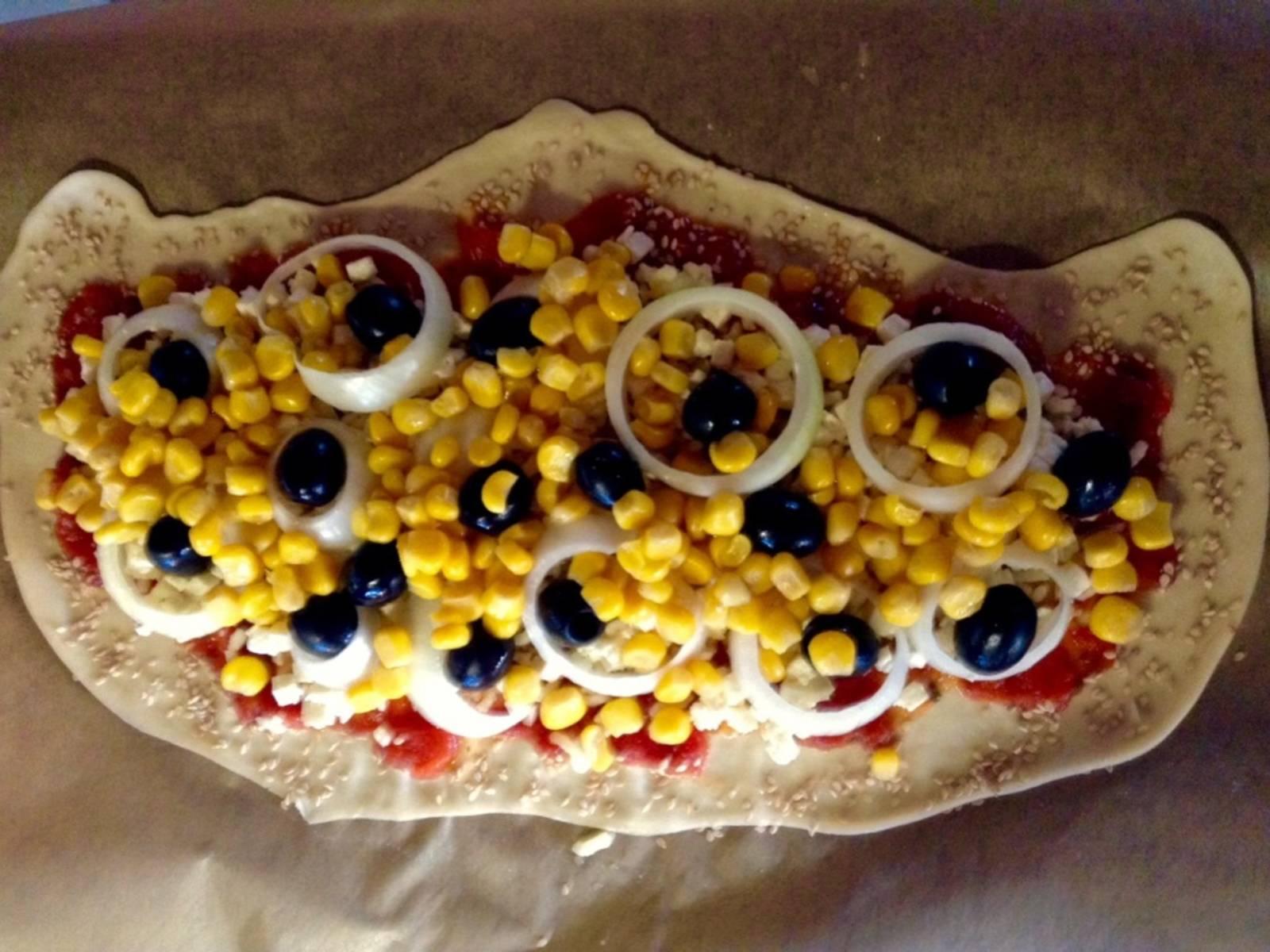 Jetzt kommt der Belag. Hier könnt ihr entweder alles draufpacken, oder aber, da das Auge ja bekanntlich mit isst, die Pizza mit den Zutaten kreativ dekorieren. Ich habe zuerst den Mais über die Pizza gestreut (vorher sehr gut abtropfen lassen), danach die Zwiebelringe draufgelegt (vorher schneiden) und dann die Oliven in die Lücken (zuvor gut abtropfen lassen).