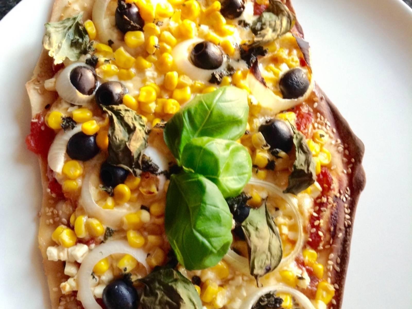 Auf die noch warme Pizza streut ihr jetzt noch etwas gehackten Oregano und einige frische Basilikumblätter fürs Auge und könnt nun diese ganz besondere Pizza genießen.