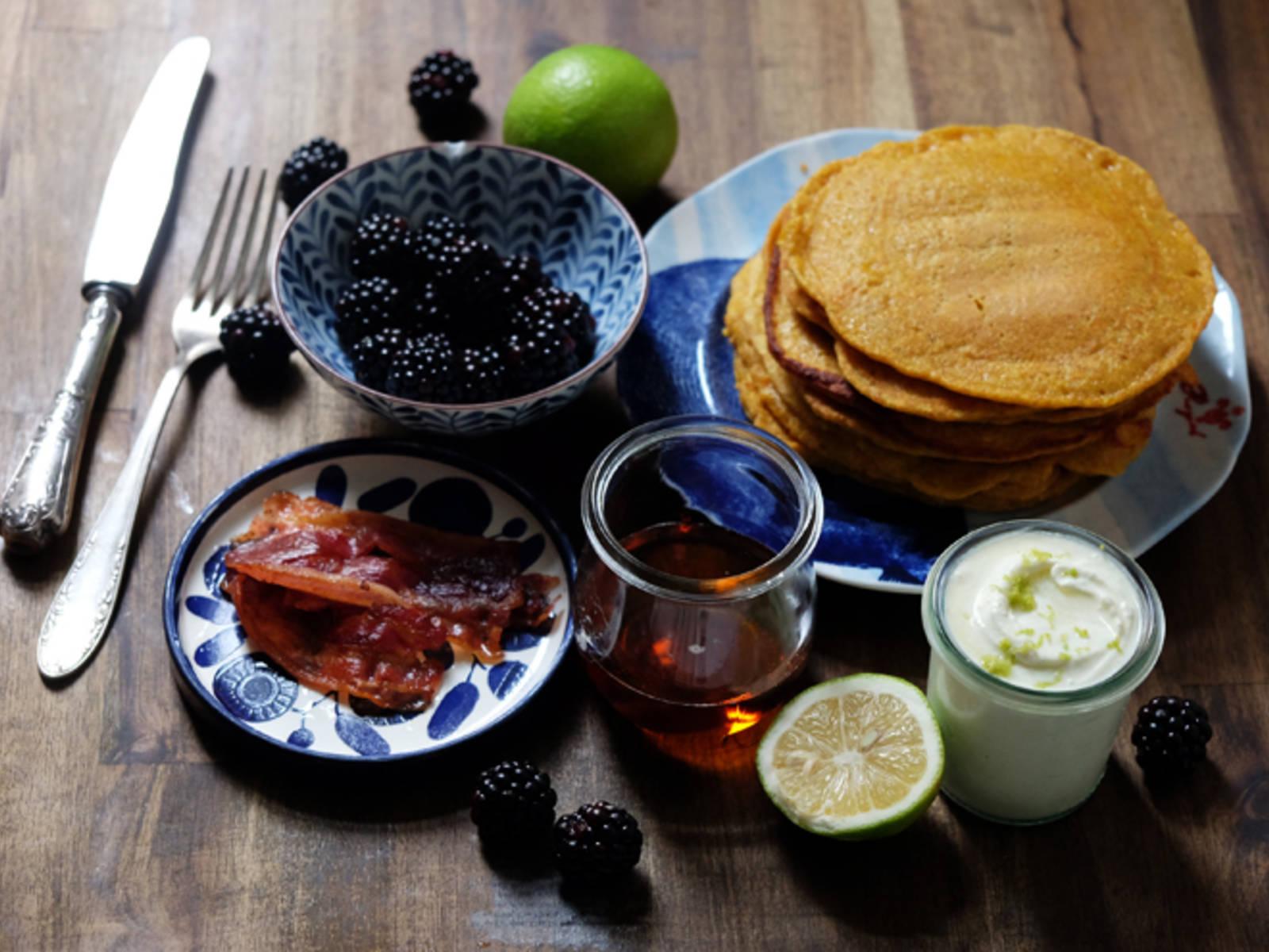 Kürbis-Pancakes zusammen mit Brombeeren, knusprigem Bacon, der Mascarpone-Creme und Ahornsirup servieren.