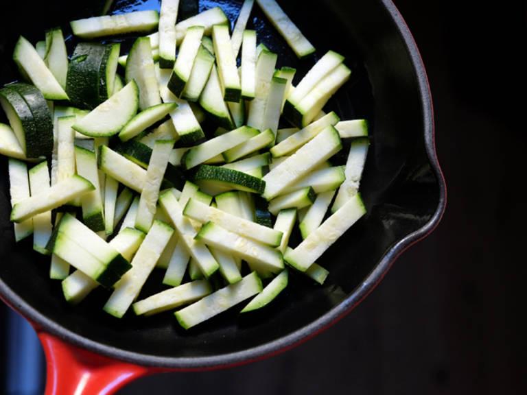 清洗西葫芦,切成细条。洋葱削皮后切丁。蒜剁碎,置于一旁。加热煎锅。往里倒入一部分澄清黄油,倒入西葫芦,中火翻炒。再加入洋葱,煎炒5-7分钟。撒盐与胡椒调味。