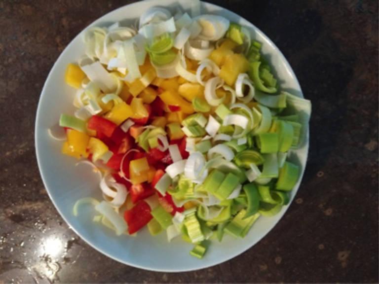 将西兰花切成小朵,胡萝卜削皮切好,倒入锅中。灯笼椒和韭葱也切好,待用。清洗藜麦并滤干。