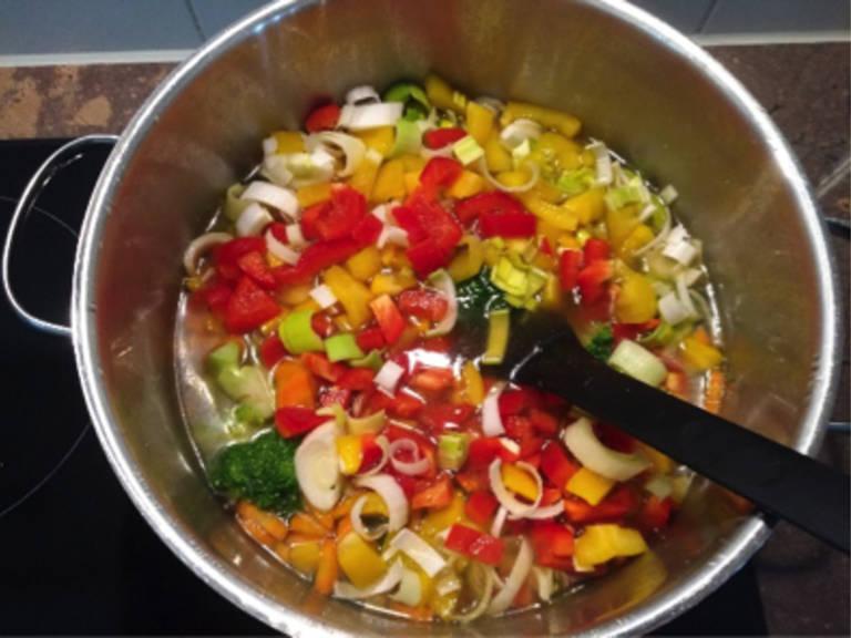 将蔬菜高汤倒入西兰花和胡萝卜中,煮沸后再煮7分钟。往里放入灯笼椒和韭葱,煮5分钟。然后放入藜麦,调至中火,再煮10分钟。关火,静置10-15分钟。将混合物倒入大碗中放凉。