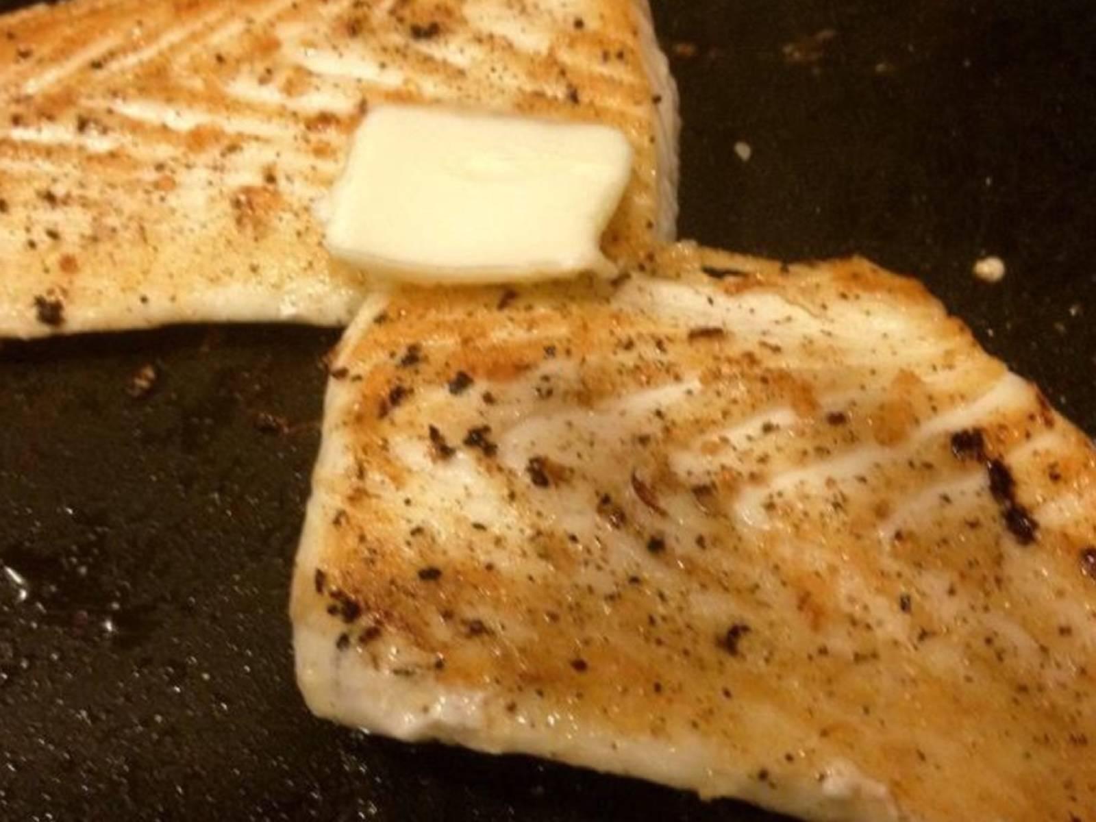 在鱼的两面撒些盐和现磨胡椒,放到培根油中煎。第一面煎4-5分钟,然后翻面。在鱼上放黄油,煎另一面3-4分钟。