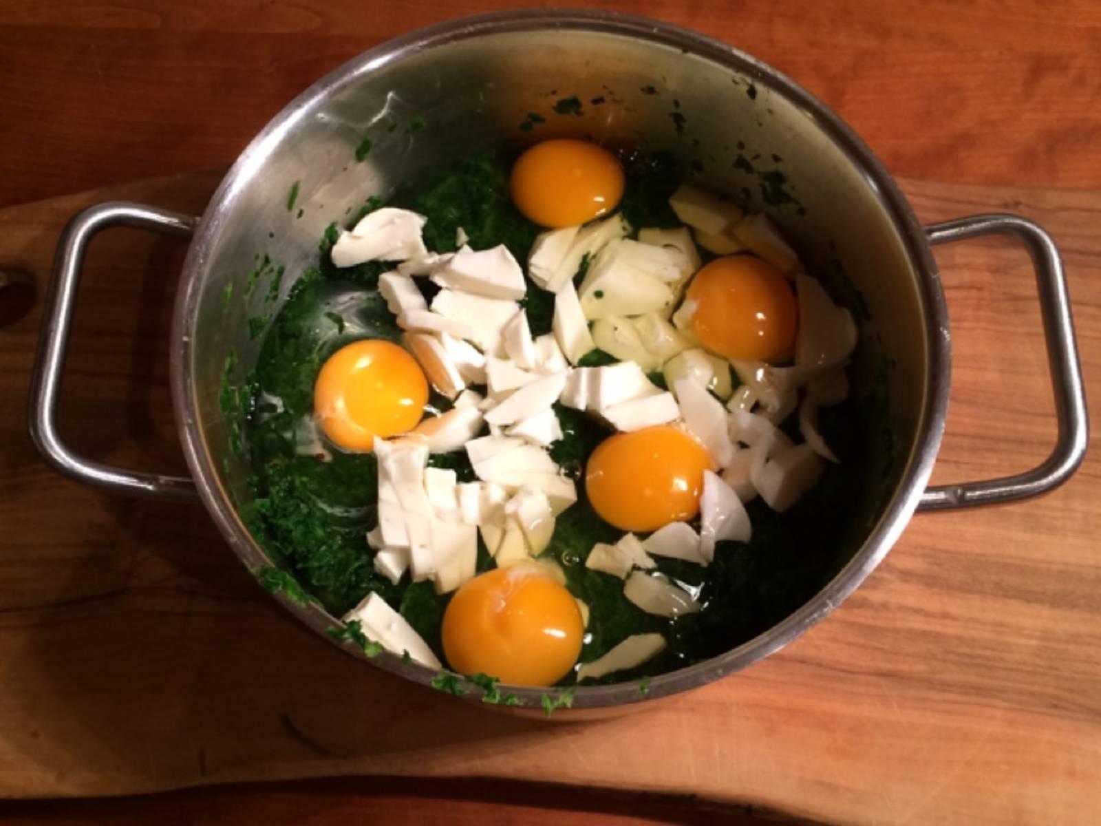 将烤箱预热至200℃。在锅中加热菠菜。此期间,剁碎马苏里拉奶酪。如果菠菜水分太多,可以用筛子辅助滤掉。将鸡蛋和马苏里拉奶酪放到锅中,和菠菜搅拌混合。
