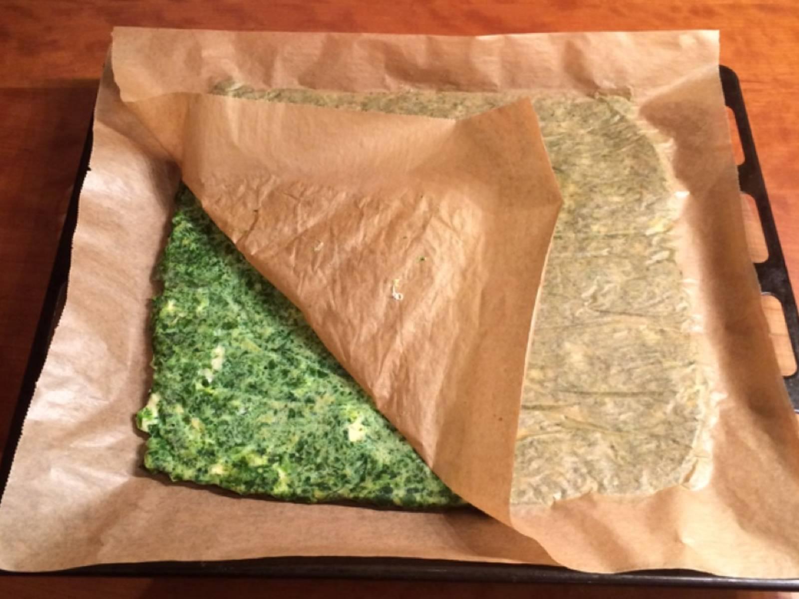 用另一张烘焙纸盖上,然后小心地将菠菜层翻面。将底部的烘焙纸撕掉,放入烤箱再烤10分钟。