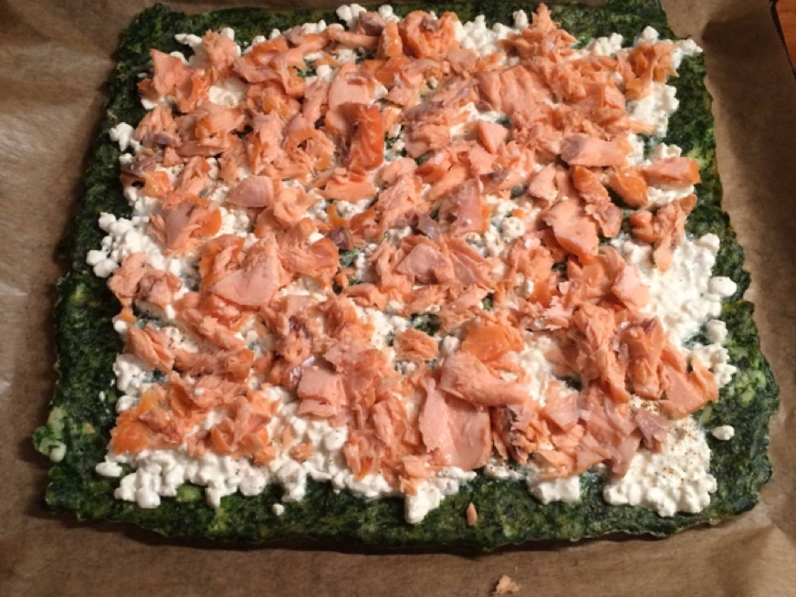 Spread the cottage cheese on top of the spinach layer and add an even layer of smoked salmon. Roll up gently into a log.
