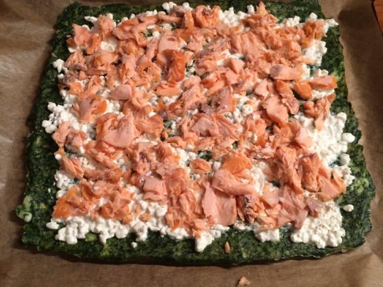 Den Hüttenkäse und den Lachs auf dem Spinat verteilen, dann vorsichtig zusammenrollen.