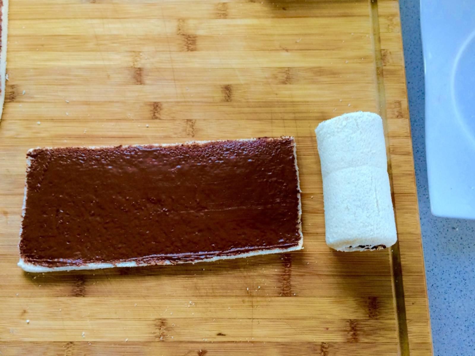 用擀面杖将吐司擀平,然后薄薄地抹上一层巧克力酱。碾碎覆盆子后放到吐司上。