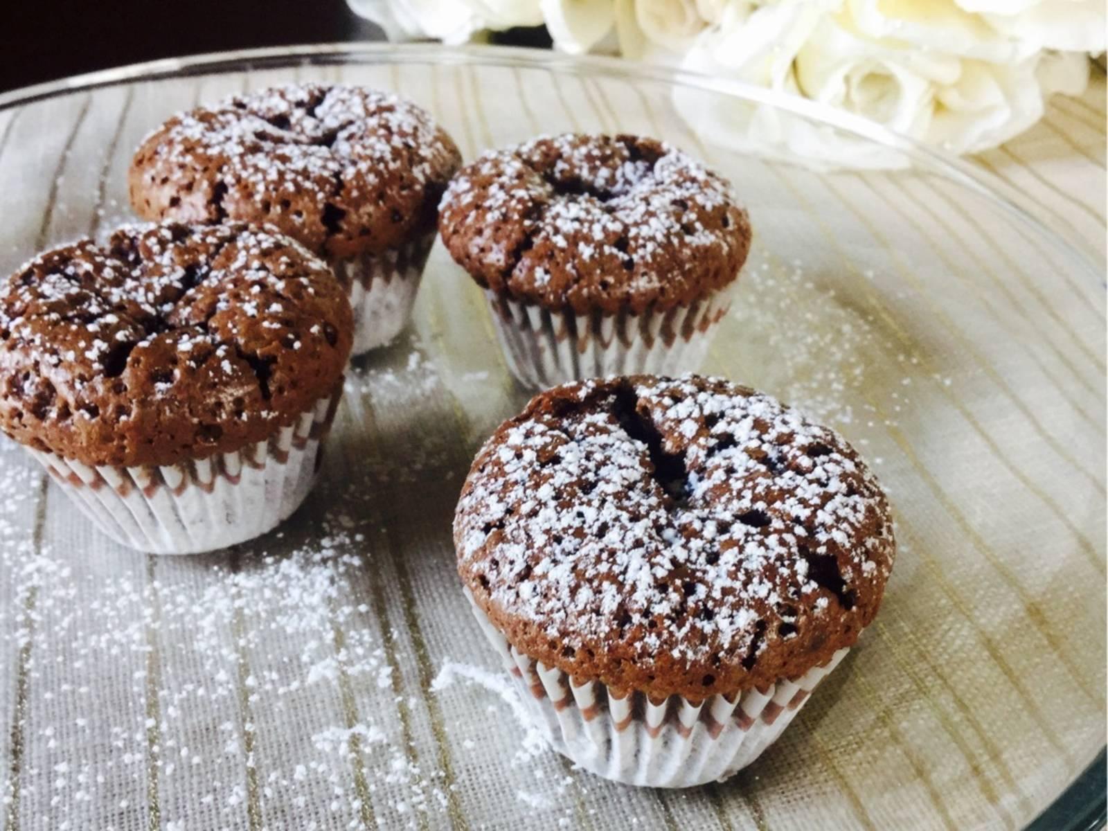 Erst Zucker, dann Eier hinzugeben und gut vermengen. Kakao- und Kaffeepulver hinzusieben, dann einen Teil des Vanilleextraktes sowie den Rum (falls erwünscht) hinzugeben und gut vermengen. Teig in die Papierförmchen füllen, bis sie 2/3 voll sind. Ca. 30 Min. bei 175°C backen. Aus dem Ofen nehmen und 5 Min. beiseite stellen. Dann aus der Muffinform nehmen und auf einem Kuchengitter kühlen.