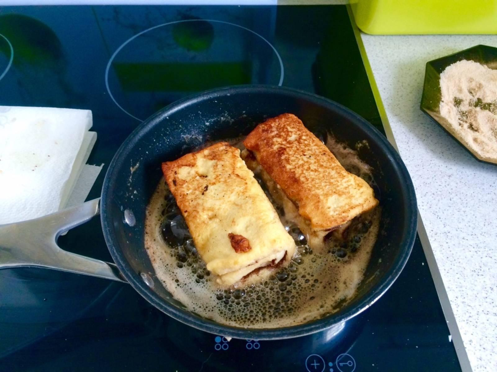 混合糖和肉桂。在煎锅中放入黄油,将吐司各面煎至金黄,用厨房纸轻拍吐司吸去油分,然后快速将吐司卷蘸上肉桂糖。