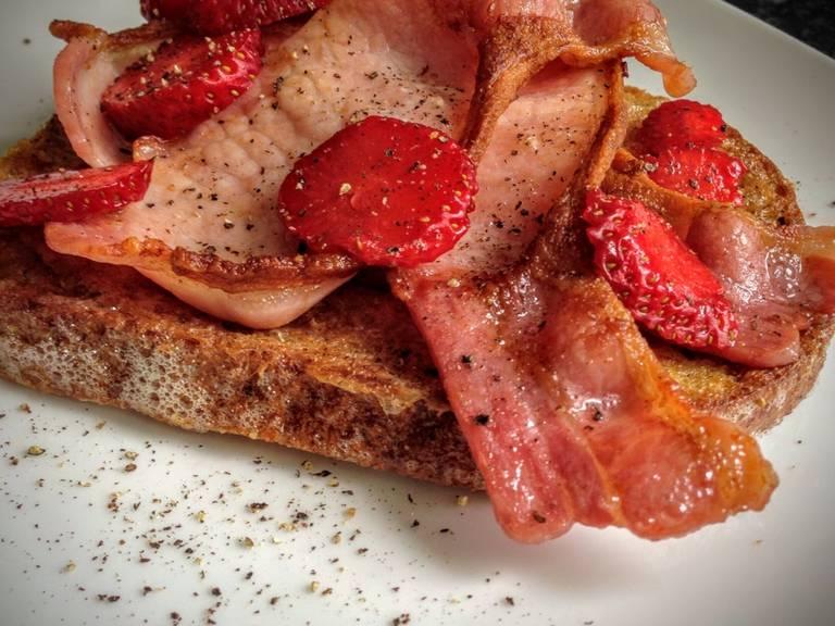 Das in Ei getränkte Brot in der Butter braten, bis es goldbraun ist. Fertig! Mit Bacon und Erdbeeren servieren und ein bisschen schwarzen Pfeffer drüber streuen. Guten Appetit!