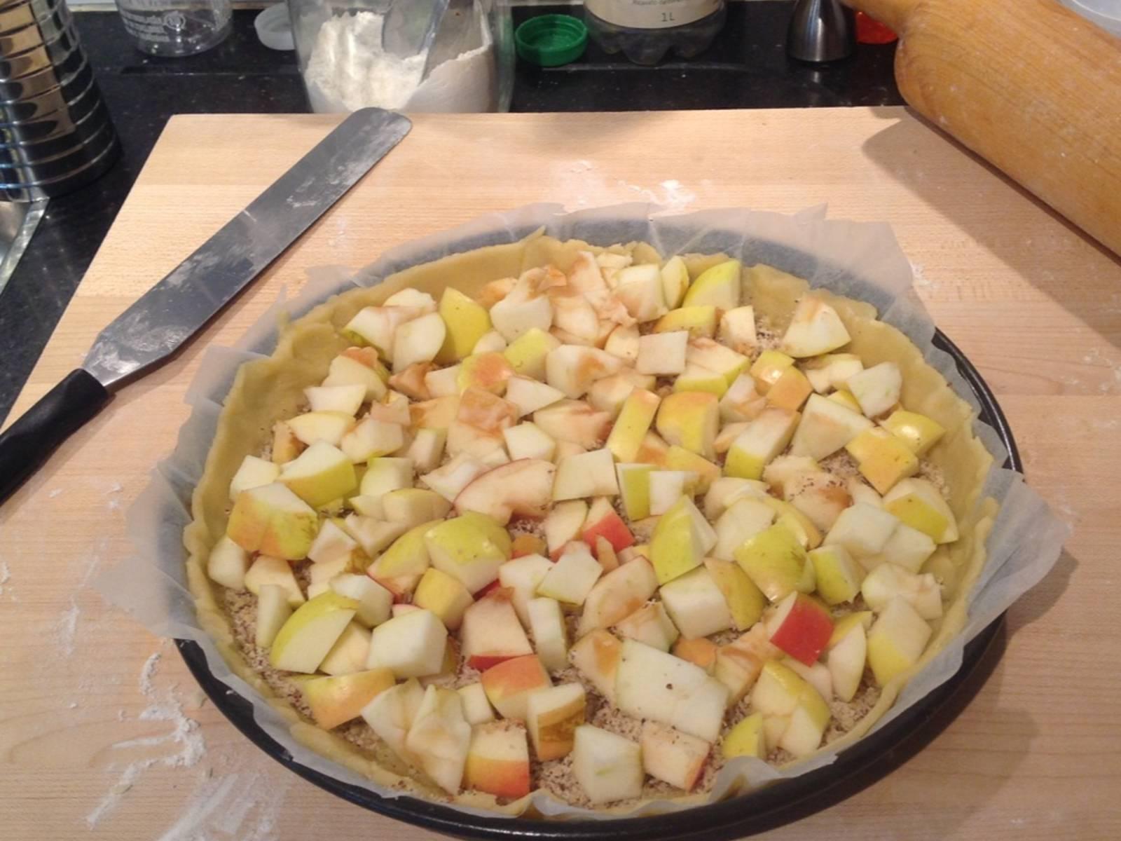 Äpfel schälen, Kerngehäuse entfernen und Äpfel in kleine Würfel schneiden. Auf dem Teigboden verteilen und den Guss sofort darüber gießen.