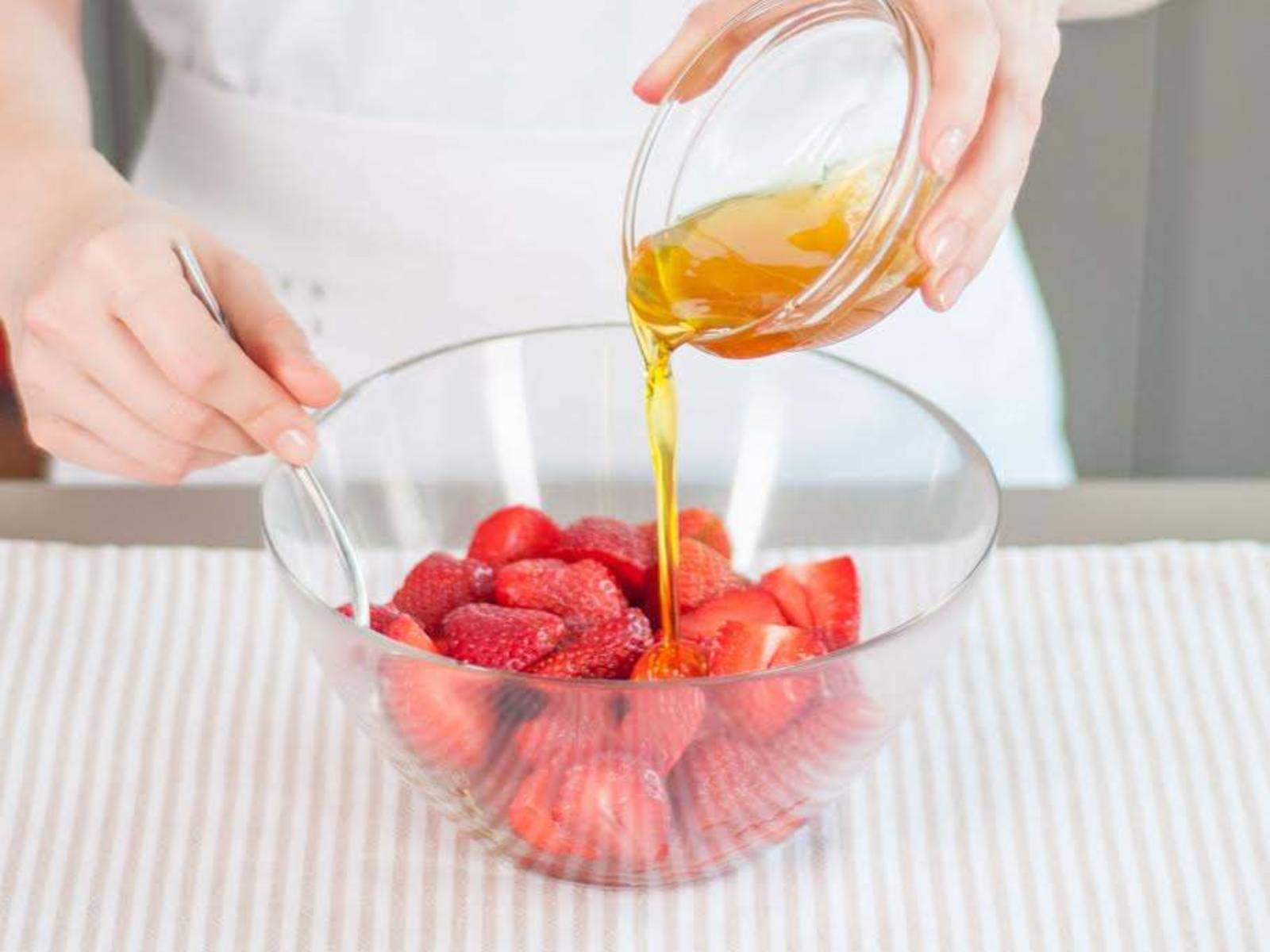 将蜂蜜、橄榄油和些许盐搅拌混合,然后倒在草莓上。翻搅,让草莓裹上酱汁。
