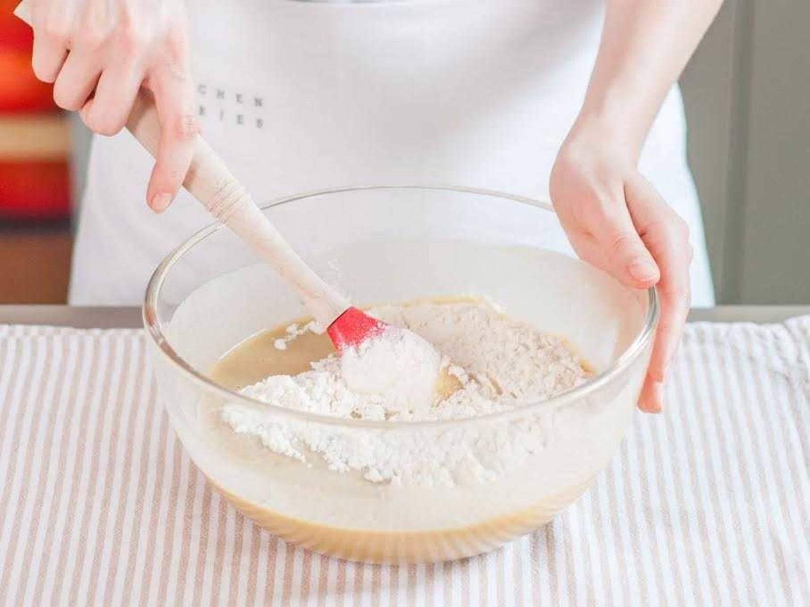 In einer separaten Schüssel Mehl, Backpulver und das restliche Salz miteinander vermengen. Eine Hälfte der Mehlmischung zur Ei-Zucker-Mischung geben. Joghurt unterrühren und anschließend die restliche Mehlmischung hinzugeben und vermengen.