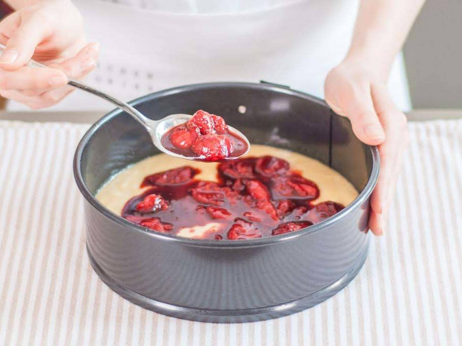 Turn oven down to 175°C/350°F. Brush springform pan with olive oil. Pour half of batter into pan, then top with roasted strawberries and their juices, stopping about half-a-thumb's length from the perimeter.