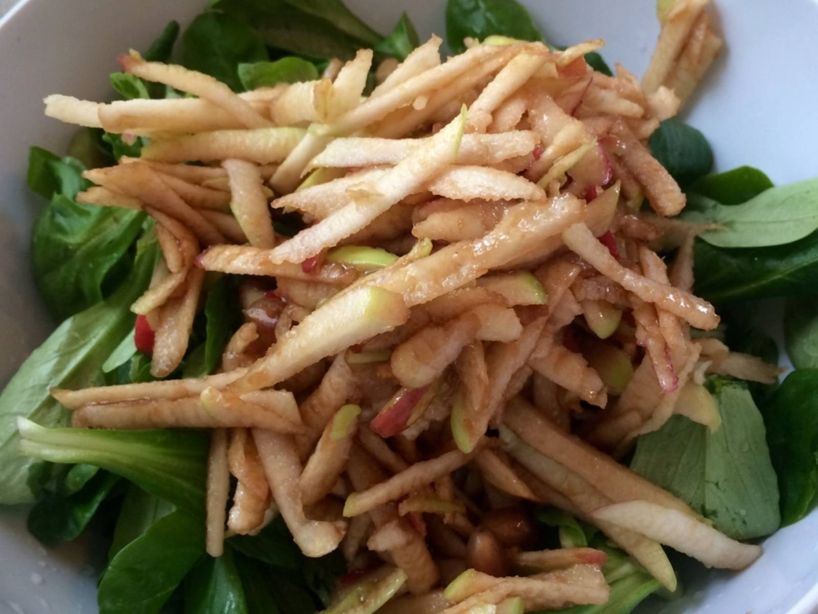 Grate apples. Combine olive oil, balsamic vinegar, and pomegranate juice, then use to marinate grated apple. Wash lamb's lettuce and put in a large bowl together with the apple.