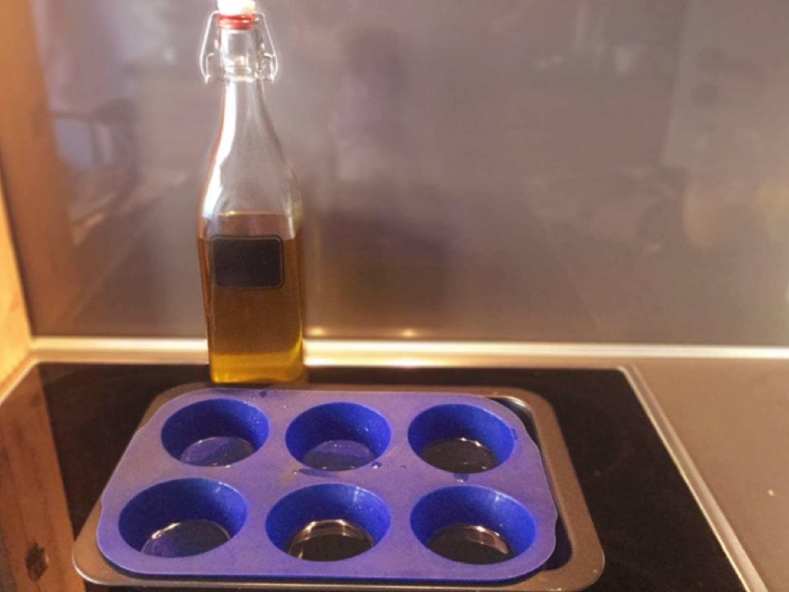 将烤箱预热至220℃。往每个玛芬杯中涂一茶匙油,润滑各面。放入烤箱中,充分热透后再取出。