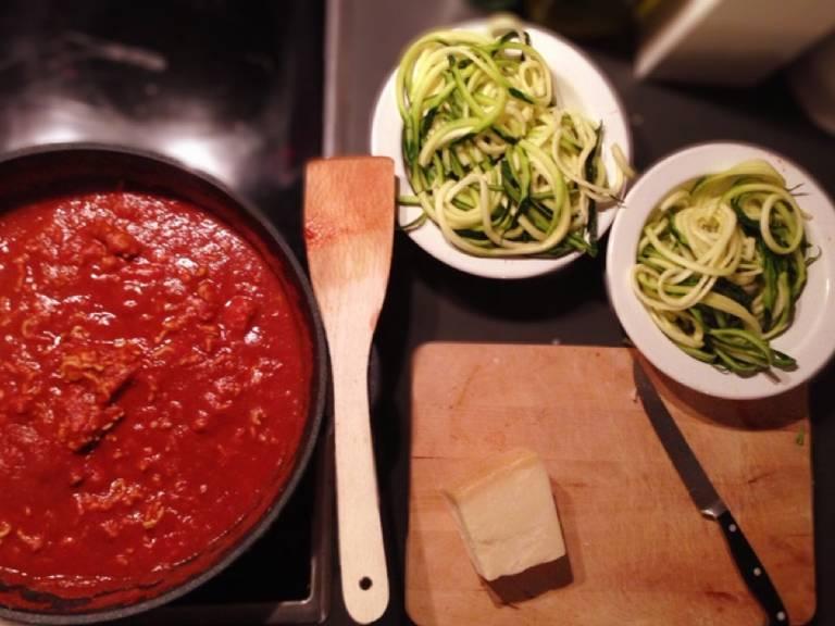 Gemüsenudeln abgießen, sofort auf Teller verteilen, Bolognese dazugeben und den Parmesan darüber reiben. Noch mit ein paar Basilikumblättern garnieren und servieren.