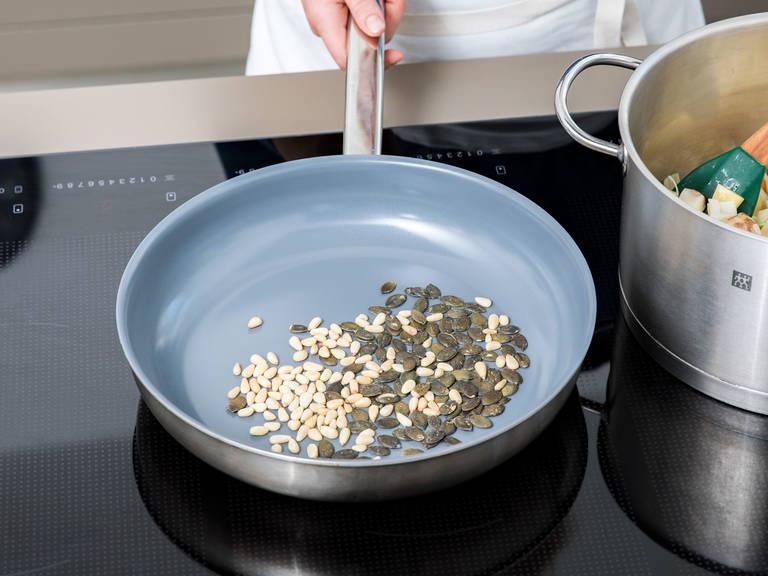 此期间,在一个煎锅中烤松子和南瓜籽,直至它们变成棕色且散发香味。倒出瓜子,置于一旁。