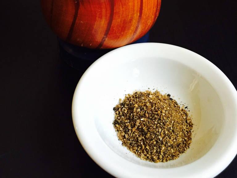 Zwiebel schälen und in dünne Scheiben schneiden. Knoblauch und Ingwer schälen und fein hacken. Tomaten würfeln. Schwarze Pfefferkörner, Koriandersamen und Kreuzkümmelsamen in einem Mörser zerstoßen und fein mahlen.