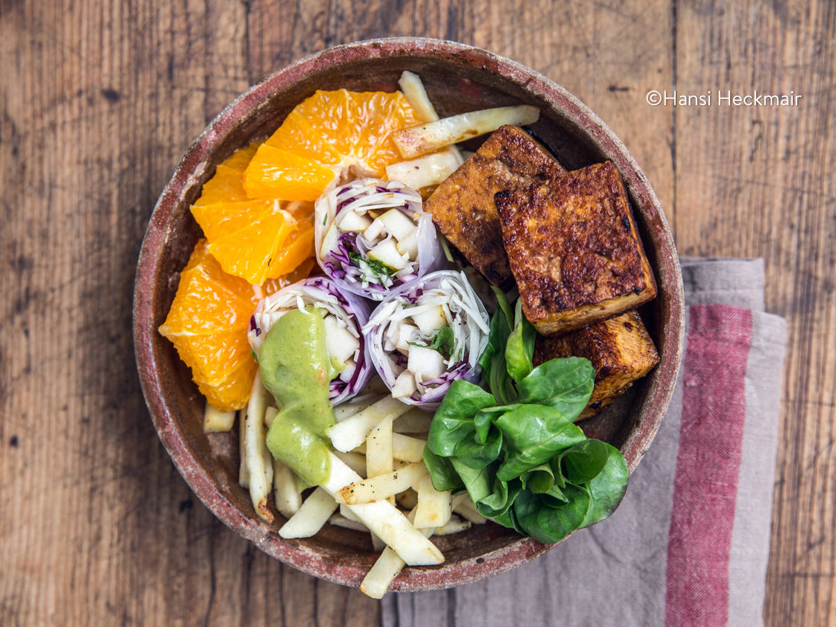 Salad bowl with summer rolls, spicy tofu, parsnips, and orange
