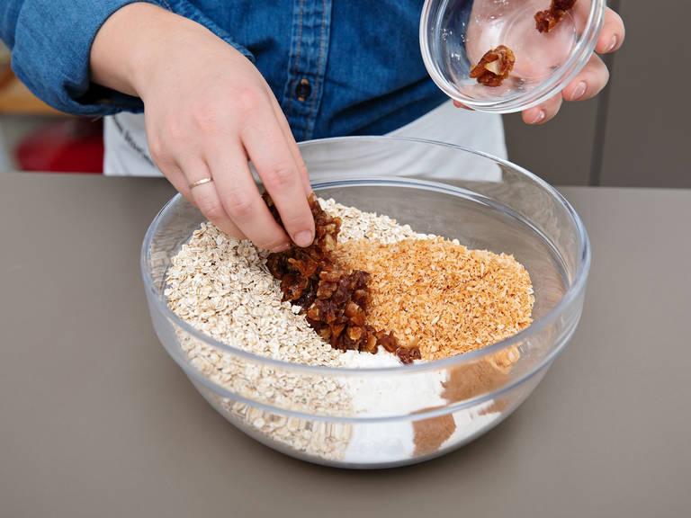Mehl, gemahlenen Zimt, Muskat, Salz, Backnatron, Haferflocken, Datteln und geröstete Kokosraspeln in einer separaten Schüssel mischen. Die Mehlmischung in die Küchenmaschine geben und mixen, bis alles vermengt ist.