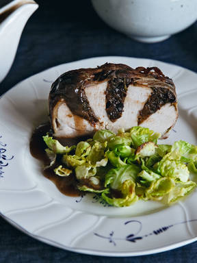 Bacon-wrapped stuffed pork loin roast with Brussels sprouts