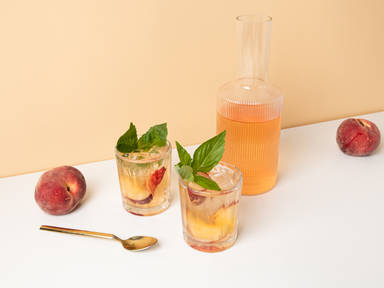 Rosé spritzer with white peaches and basil