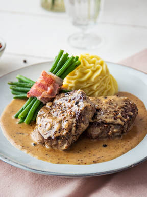 Classic steak au poivre (French pepper steak) with mashed potatoes and green bean bundles